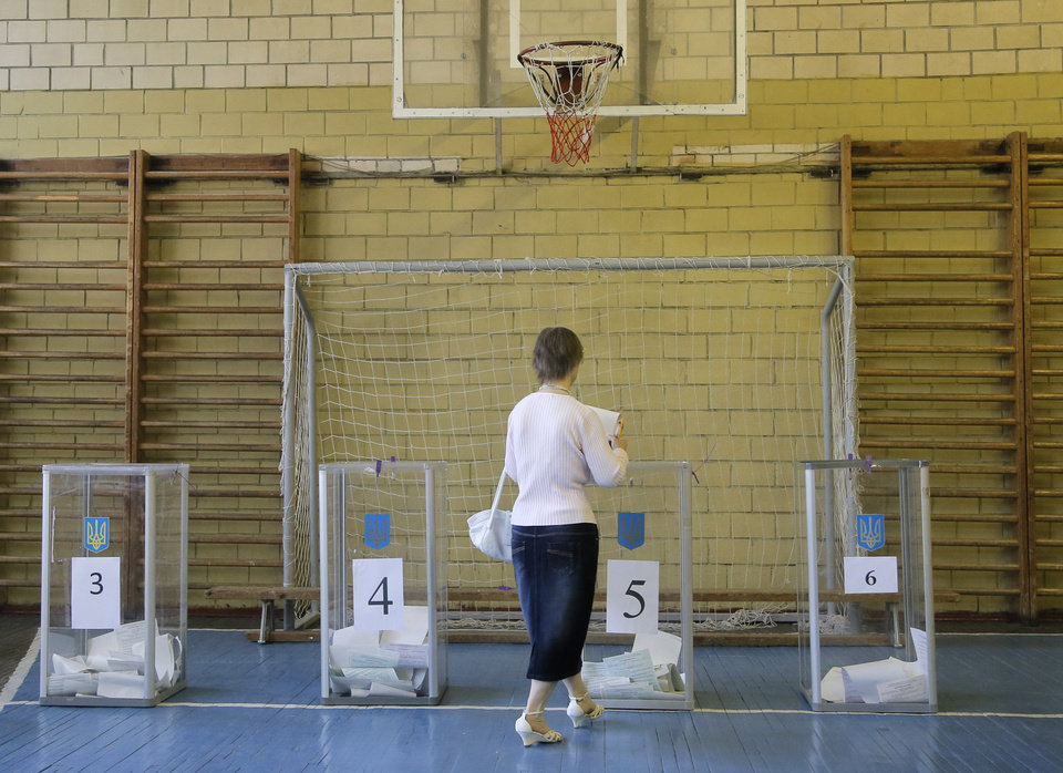 Photo - A Ukrainian woman casts her ballot at a polling station during presidential election in Kiev, Ukraine, Sunday, May 25, 2014.  Ukraine's critical presidential election got underway Sunday under the wary scrutiny of a world eager for stability in a country rocked by a deadly uprising in the east. (AP Photo/Efrem Lukatsky)