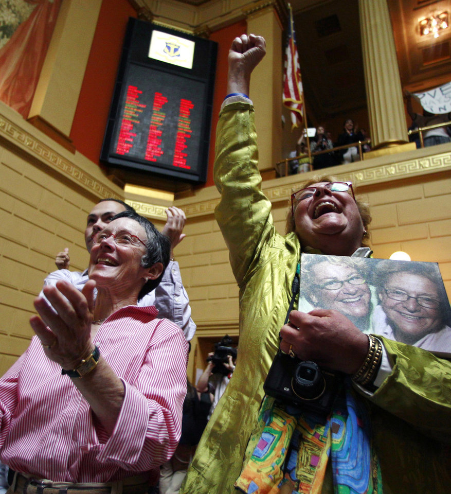 Photo - Lise Iwon, right, Julie Smith celebrate after a gay marriage bill passed a vote in the Rhode Island House at the State House in Providence, R.I., Thursday, May 2, 2013. (AP Photo/Charles Krupa)