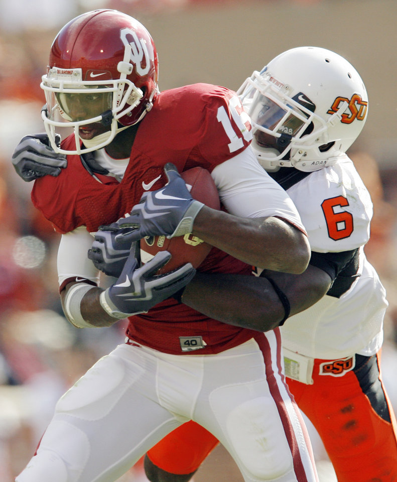 Photo - OU's Jaz Reynolds (16) is taken down by Andrew McGee (6) of Oklahoma State after a catch in the first quarter of the Bedlam college football game between the University of Oklahoma Sooners (OU) and the Oklahoma State University Cowboys (OSU) at the Gaylord Family-Oklahoma Memorial Stadium on Saturday, Nov. 28, 2009, in Norman, Okla.