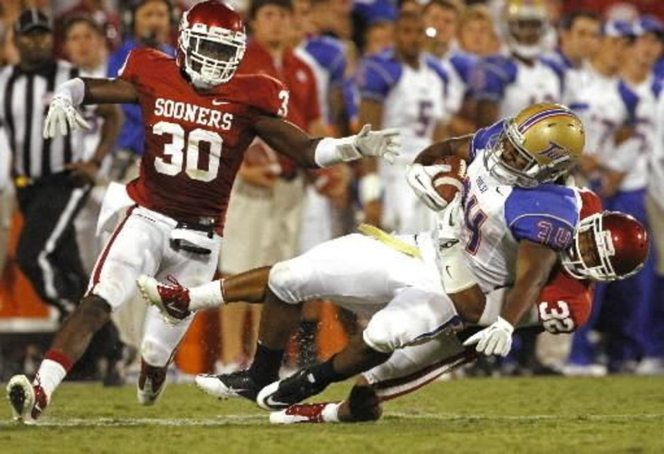 Photo - Oklahoma's Javon Harris (30) and Oklahoma's Jamell Fleming (32) take down Tulsa's Willie Carter (34) after a long pass play during the second half of the college football game between the University of Oklahoma Sooners ( OU) and the Tulsa University Hurricanes (TU) at the Gaylord Family-Memorial Stadium on Saturday, Sept. 3, 2011, in Norman, Okla. Photo by Steve Sisney, The Oklahoman ORG XMIT: KOD