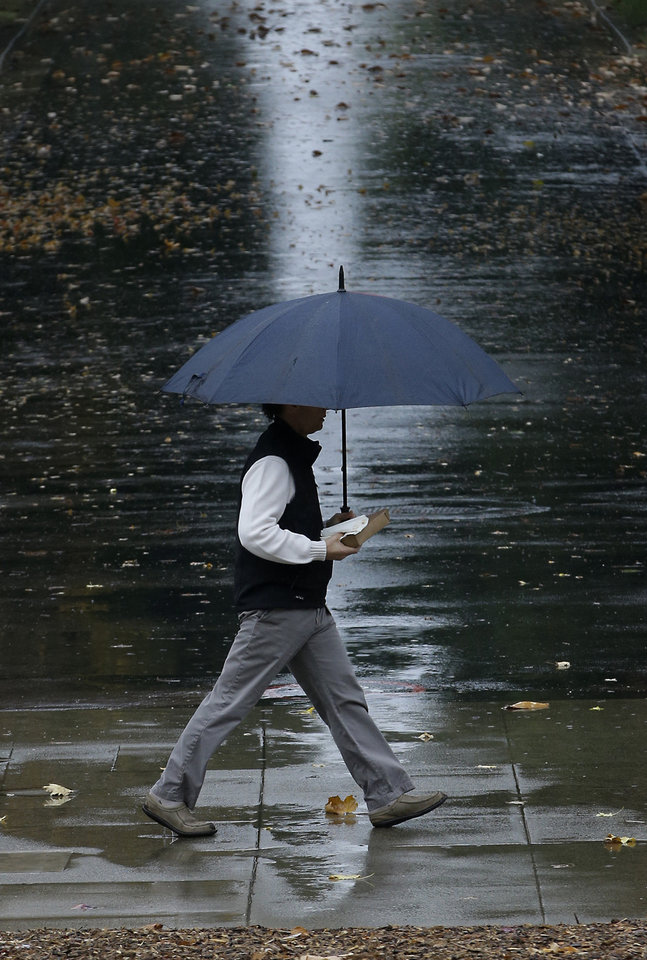 Photo - A pedestrian uses an umbrella as a storm passes through Sacramento, Calif., Thursday, Dec. 3, 2015. The first storm of December brought much needed rain to the valley and snow to the Sierra Nevada.(AP Photo/Rich Pedroncelli)