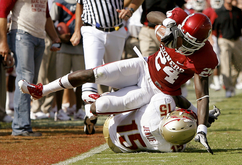 Photo - OU's Dejuan Miller lands on Florida State's Ochuko Jenije during the first half of the college football game between the University of Oklahoma Sooners (OU) and Florida State University Seminoles (FSU) at the Gaylord Family-Oklahoma Memorial Stadium on Saturday, Sept. 11, 2010, in Norman, Okla.   Photo by Bryan Terry, The Oklahoman