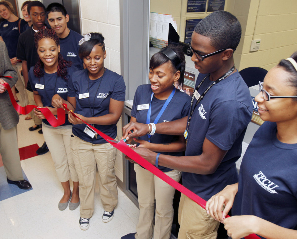 Photo - John Marshall High School students Brianna Johnson and Tyler Harrison cut a ribbon during a ceremony for the opening of the Tinker Federal Credit Union branch at the school in Oklahoma City. Photo by Paul Hellstern, The Oklahoman  PAUL HELLSTERN