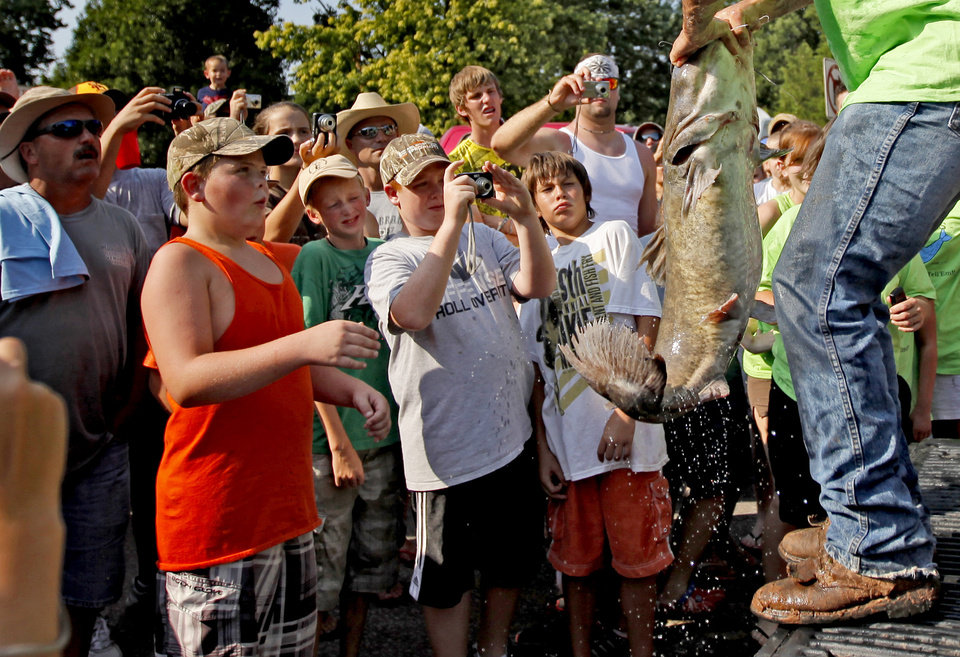 Fans watch as a catfish is brought in during the Okie Noodling Tournament in Pauls Valley on Saturday. (Photo by Bryan Terry, The Oklahoman)