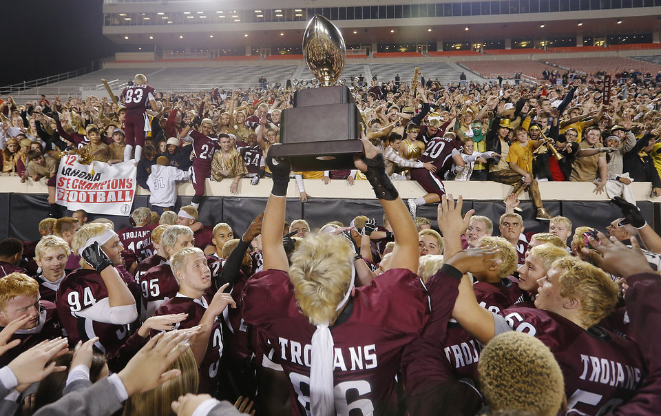 Photo - CLASS 6A HIGH SCHOOL FOOTBALL STATE CHAMPIONSHIP GAME: Jenks' Austin Martin (86) hoist the trophy for the Trojan fans during the Class 6A Oklahoma state championship football game between Norman North High School and Jenks High School at Boone Pickens Stadium on Friday, Nov. 30, 2012, in Stillwater, Okla.   Photo by Chris Landsberger, The Oklahoman