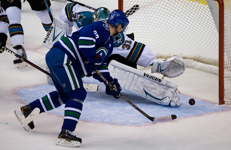 Photo - Vancouver Canucks' Henrik Sedin, of Sweden, scores against San Jose Sharks' goalie Antti Niemi, of Finland, during the second period of an NHL hockey game in Vancouver, British Columbia, Tuesday, March 5, 2013. (AP Photo/The Canadian Press, Darryl Dyck)