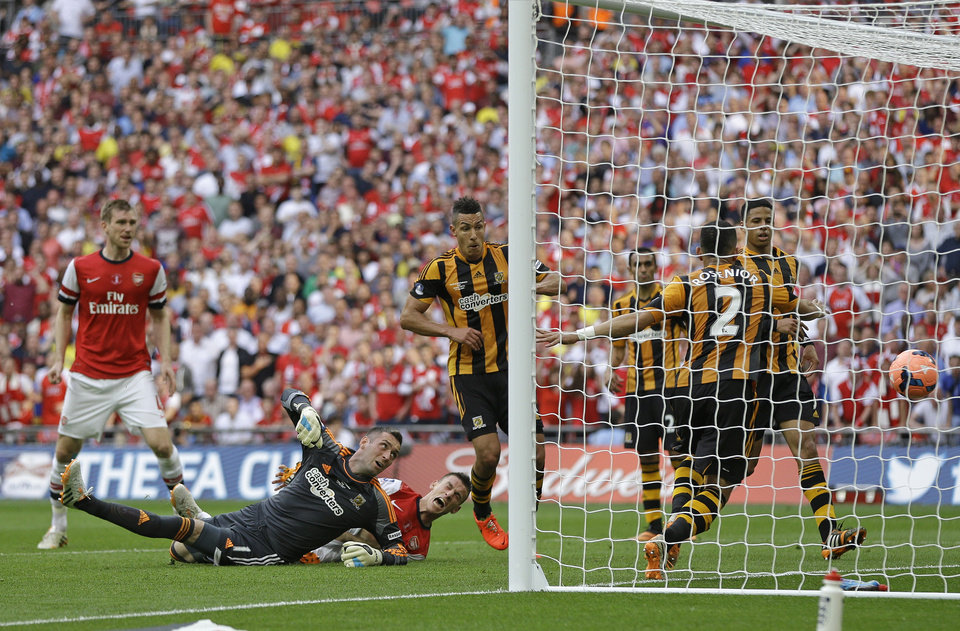 Photo - Arsenal's Laurent Koscielny, bottom centre,  scores his sides second goal during the English FA Cup final soccer match between Arsenal and Hull City at Wembley Stadium in London, Saturday, May 17, 2014. (AP Photo/Kirsty Wigglesworth)
