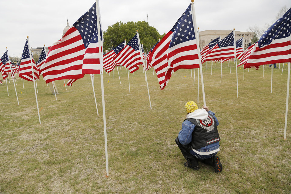 Kim Mattheson, with Bikers Against Child Abuse helps to plant American flags in honor of children who died in America in 2011 in the fields south of the state Capitol Sunday, April 7, 2013. Photo by Doug Hoke, The Oklahoman