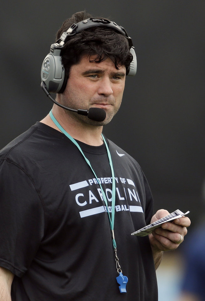 Photo - In this photo taken Wednesday, April 9, 2014 North Carolina's new assistant head coach for offense and tight ends Seth Littrell watches during an NCAA college football spring practice in Chapel Hill, N.C. After spending the last two seasons at Indiana, Littrell is preparing for his first season with the Tar Heels. (AP Photo/Gerry Broome)