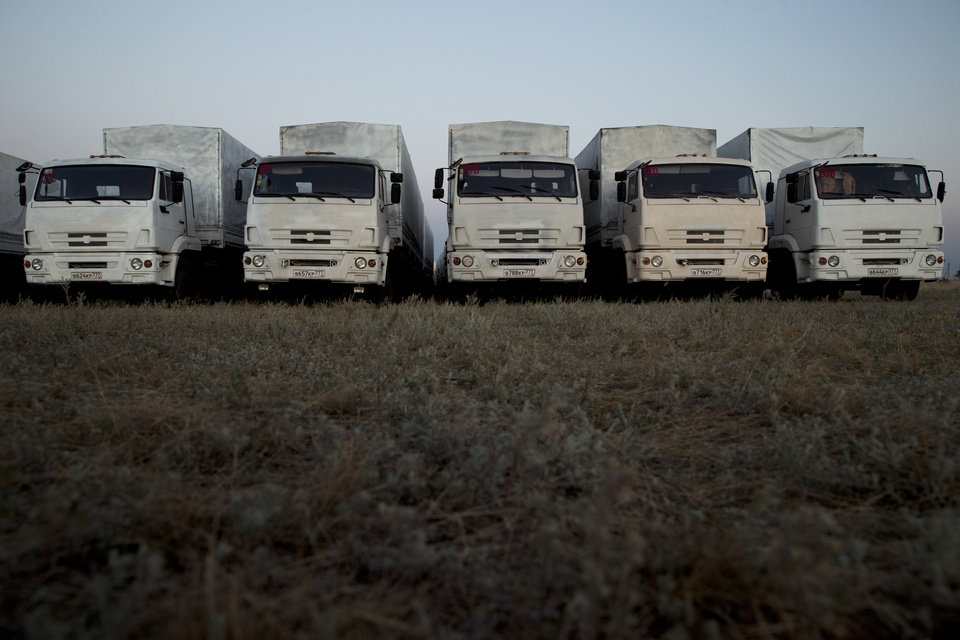 Photo - About 60 trucks forming part of a Russian aid convoy are parked in a field about 7 kilometers (4 miles) from a border control point with Ukraine in the Russian town of Donetsk, Rostov-on-Don region, Russia, Thursday evening, Aug. 21, 2014. (AP Photo/Pavel Golovkin)
