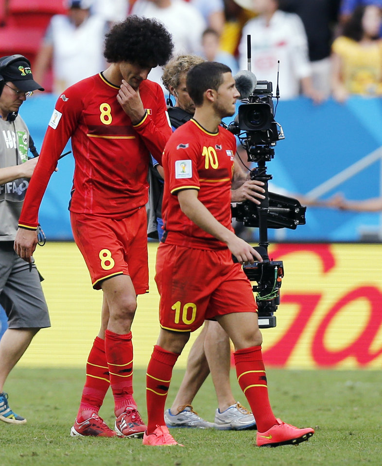 Photo - Belgium's Eden Hazard (10) and Marouane Fellaini are filmed as they walk off the pitch following Argentina's 1-0 victory over Belgium after  the World Cup quarterfinal soccer match at the Estadio Nacional in Brasilia, Brazil, Saturday, July 5, 2014. (AP Photo/Victor R. Caivano)