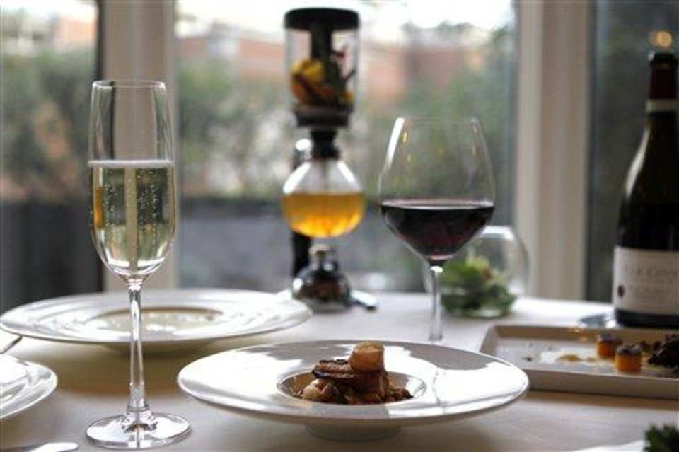 In this Dec. 7, 2012 photo, braised pork belly with gulf shrimp, white bean cassoulet, garlic jus and fried baby sage, by executive chef Kristin Butterworth, is seen with wine pairings and cafe brulot in a tea siphon, center rear, at the Grill Room of the Windsor Court Hotel in New Orleans. Roughly 50 restaurants in New Orleans are reviving an old Creole custom called reveillon, which stems from the old French tradition of eating a lavish meal after midnight Mass on Christmas Eve. (AP Photo/Gerald Herbert)