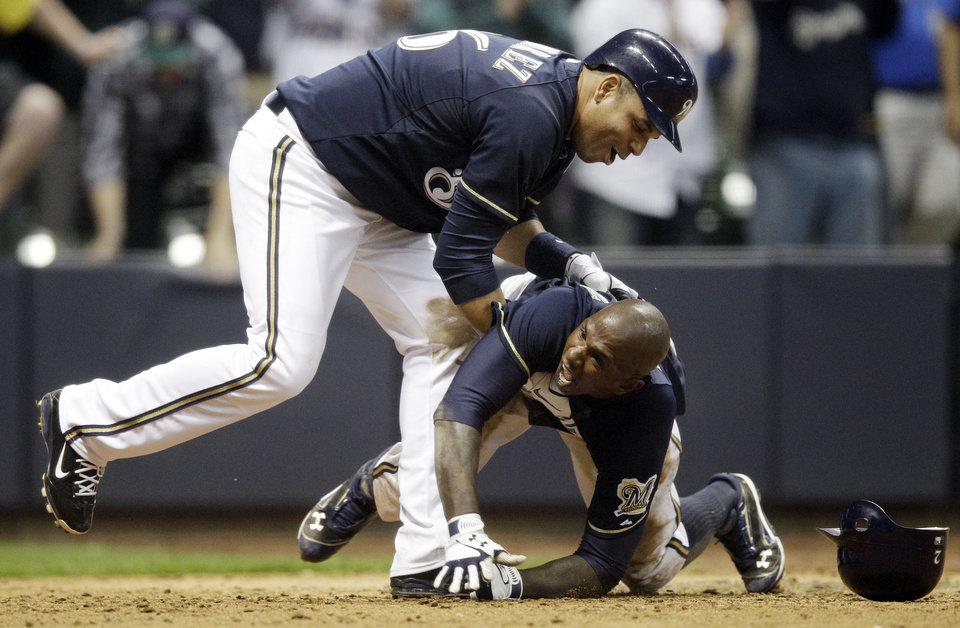 Photo -   Milwaukee Brewers' Nyjer Morgan, bottom, celebrates with Aramis Ramirez (16) after scoring from third on a sacrifice fly by Ryan Braun during the 10th inning of a baseball game against the Los Angeles Dodgers, Wednesday, April 18, 2012, in Milwaukee. The Brewers won 3-2. (AP Photo/Morry Gash)
