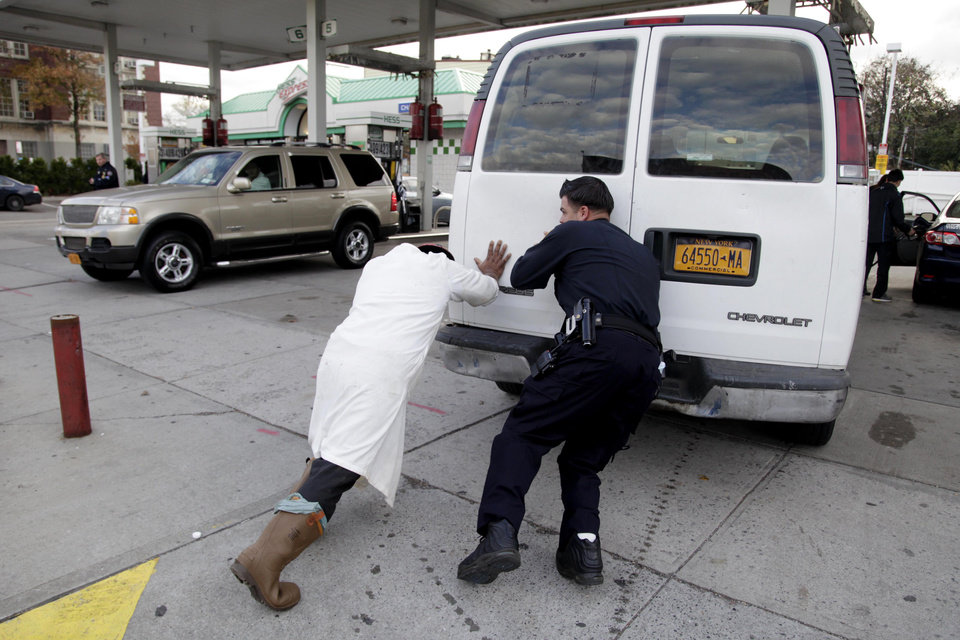 A police officer, right, helps Jason Bravo push an out-of-gas van into a gas station in the Brooklyn borough of New York, Friday, Nov. 2, 2012.   In parts of New York and New Jersey, drivers face another day of lining up for hours at gas stations struggling to stay supplied.  Superstorm Sandy damaged ports that accept fuel tankers and flooded underground equipment that sends fuel through pipelines. Without power, fuel terminals can't pump gasoline onto tanker trucks, and gas stations can't pump fuel into customers' cars.  (AP Photo/Seth Wenig) ORG XMIT: NYSW105