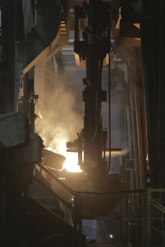Photo -  In this photo from May 12, 2014, molten metal pours out of a furnace at Rochester Metal Products Corp. in Rochester, Ind. The hulking induction furnaces the plant uses to melt scrap iron consume enough electricity to power 7,000 households. AP Photo   AJ Mast -