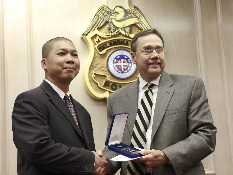 Photo - Oklahoma City police Sgt. Taylor Dinh, left, is promoted to the rank of lieutenant Thursday by Chief Bill Citty. Dinh, an 18-year police veteran, is the first Vietnamese-American promoted to lieutenant in the Oklahoma City Police Department's history. Photo by David McDaniel, The Oklahoman