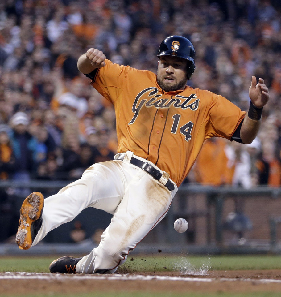 Photo - San Francisco Giants' Brandon Hicks slides after being hit with the ball to score in the fifth inning of a baseball game against the New York Mets, Friday, June 6, 2014, in San Francisco. Hicks scored on a sacrifice fly by Brandon Crawford. (AP Photo/Ben Margot)