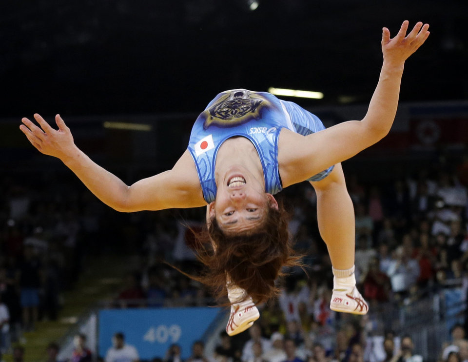 Photo -   Saori Yoshida of Japan celebrates by doing a backflip after she beat Tonya Lynn Verbeek of Canada for the gold medal during their 55-kg women's freestyle wrestling competition at the 2012 Summer Olympics, Thursday, Aug. 9, 2012, in London. (AP Photo/Paul Sancya)