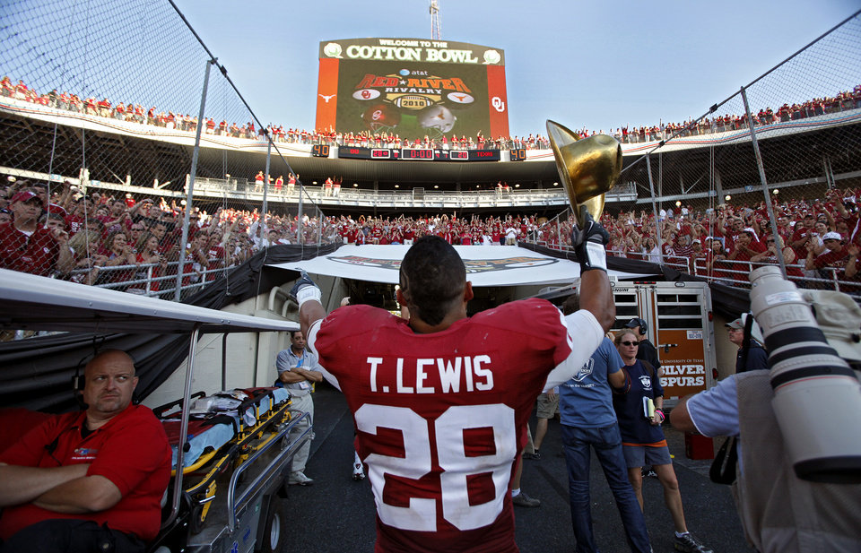 Photo - Oklahoma's Travis Lewis (28) salutes the fans as he carries the Golden Hat Trophy while walking off the field after the Sooners' 28-20 win over Texas in the Red River Rivalry college football game between the University of Oklahoma Sooners (OU) and the University of Texas Longhorns (UT) at the Cotton Bowl on Saturday, Oct. 2, 2010, in Dallas, Texas.   Photo by Chris Landsberger, The Oklahoman