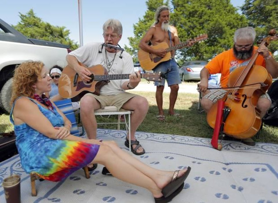 Photo -  Robbie Larsen, Steve Larsen, Dave Johnson and Charley Reeves play music at the campgrounds during the Woody Guthrie Festival in Okemah, Okla., Friday, July 11, 2014. Photo by Sarah Phipps, The Oklahoman