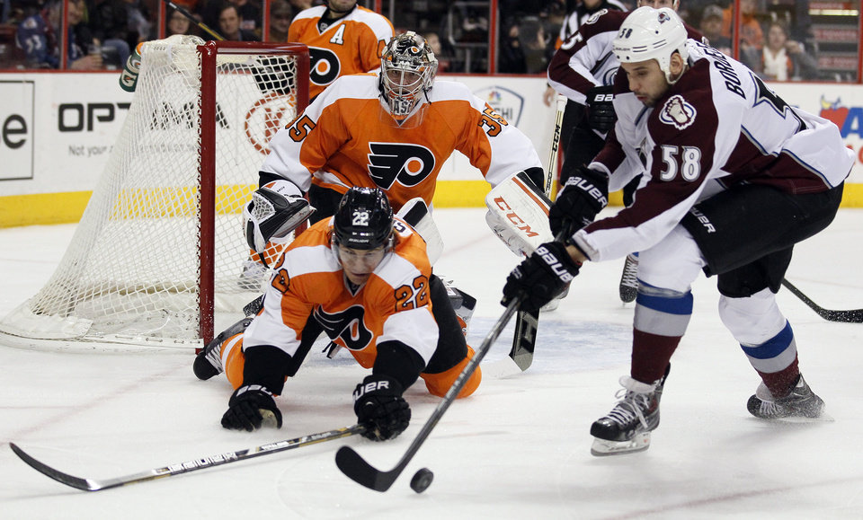 Photo - Philadelphia Flyers' Luke Schenn, left, and Colorado Avalanche' Patrick Bordeleau, right, reach for the loose puck while goalie Steve Mason looks on during the first period of an NHL hockey game, Thursday, Feb. 6, 2014, in Philadelphia. (AP Photo/Tom Mihalek)