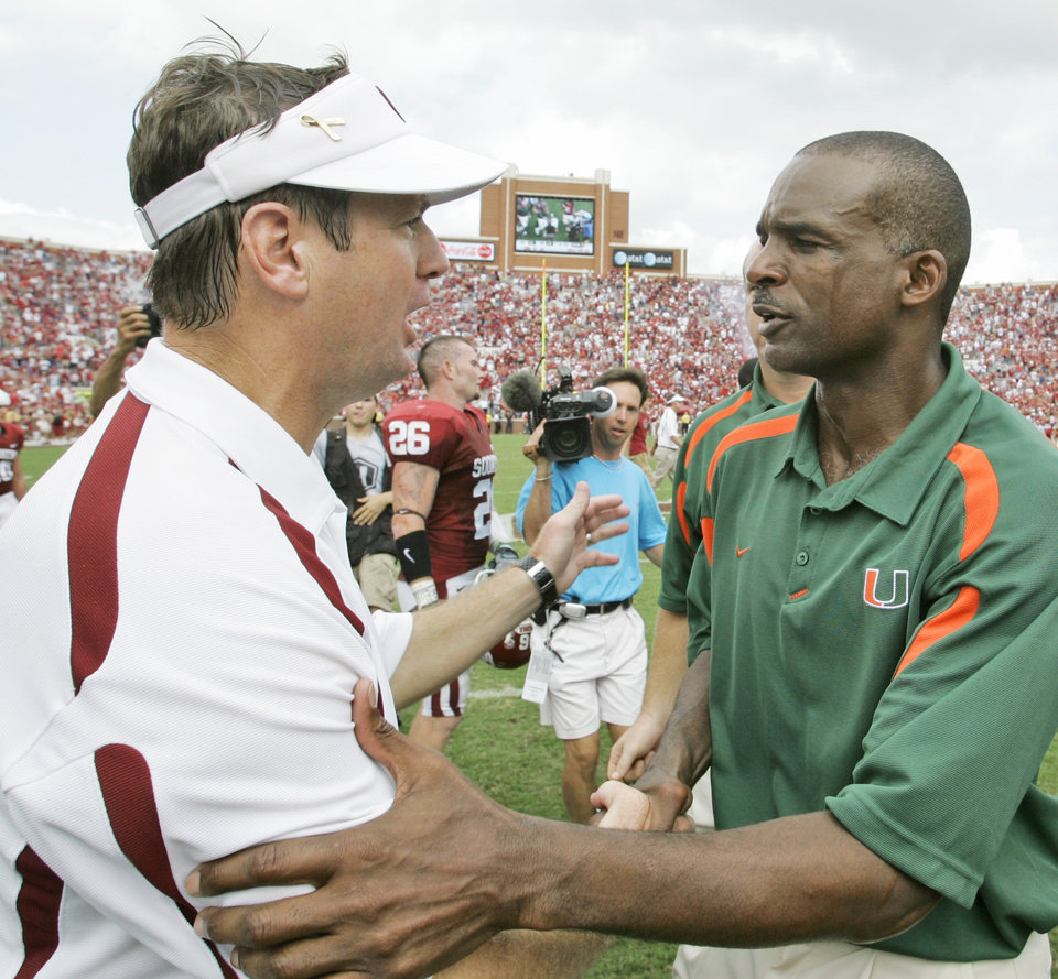 Photo - Oklahoma coach Bob Stoops, left, and former Miami coach Randy Shannon greet one another following Oklahoma's 51-13 victory over Miami on Sept. 8, 2007. Shannon could be another potential replacement for Brent Venables. AP Photo