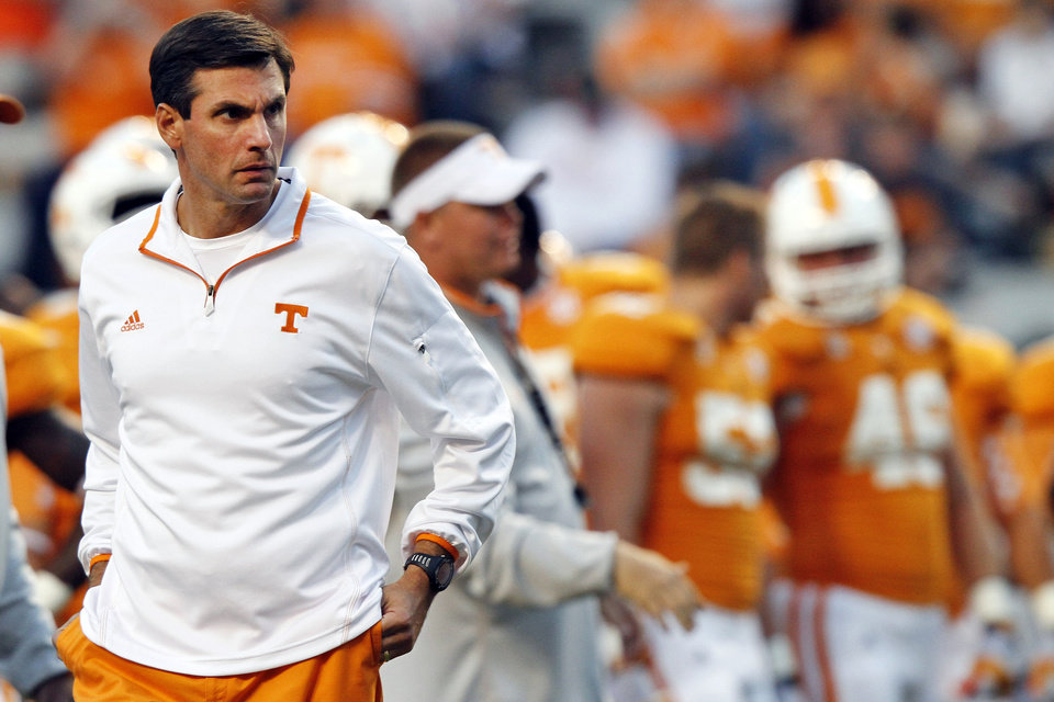 FILE- In this Sept. 22, 2012, file photo, Tennessee head coach Derek Dooley watches his team warm up before an NCAA college football game against Akron in Knoxville, Tenn. Dooley working from the press box Saturday as he recovers from hip surgery, the rest of his staff is preparing to adjust to his absence from the sidelines. The change in routine comes as the Volunteers prepare for a critical game at No. 19 Mississippi State. (AP Photo/Wade Payne, File)