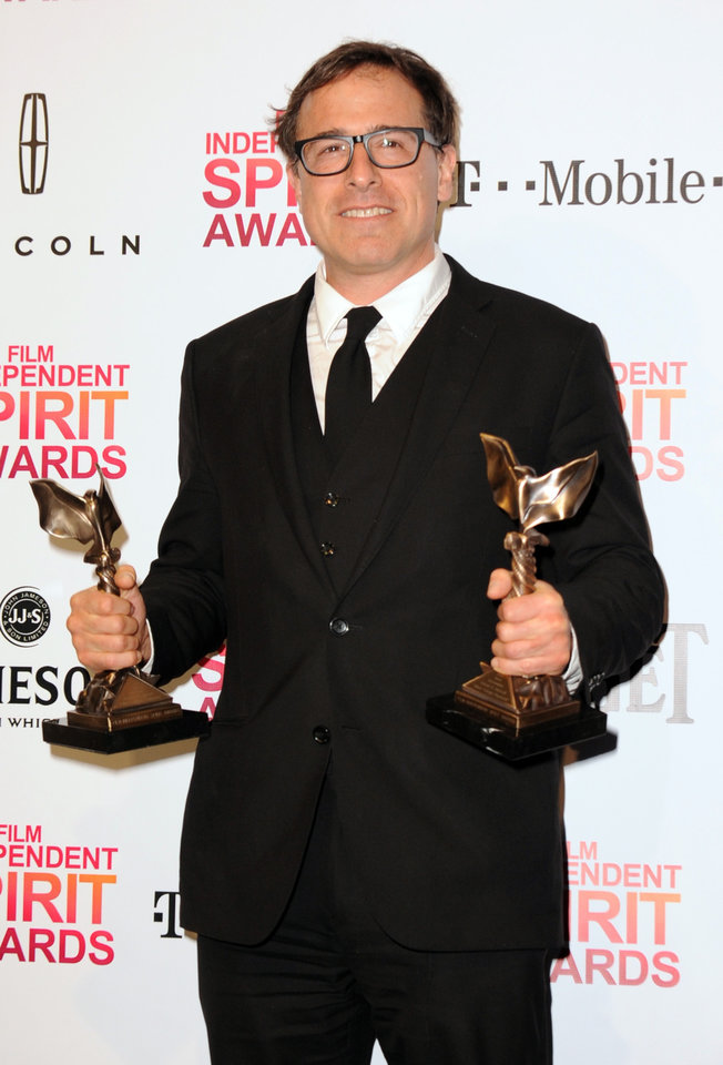 Director David O. Russell poses backstage with the awards for best director and best screenplay for