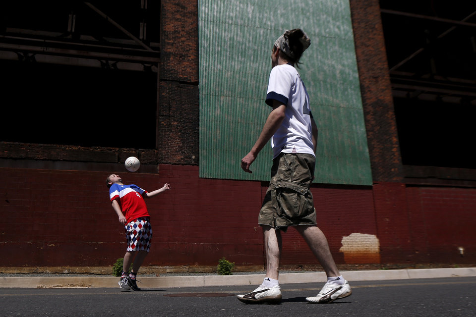 Photo - Jason Burke, 35, left, and Simon Collum, 35, both from Ridgewood, N.J., play soccer near a warehouse adjacent to Red Bull Arena before the start of an international soccer friendly between Turkey and the United States, Sunday, June 1, 2014, in Harrison, N.J. (AP Photo/Julio Cortez)