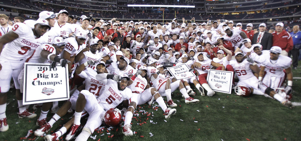 Photo - The Sooners pose with the Big 12 Championship trophy after the 23-20 win over Nebraska during the Big 12 football championship game between the University of Oklahoma Sooners (OU) and the University of Nebraska Cornhuskers (NU) at Cowboys Stadium on Saturday, Dec. 4, 2010, in Arlington, Texas.  Photo by Chris Landsberger, The Oklahoman