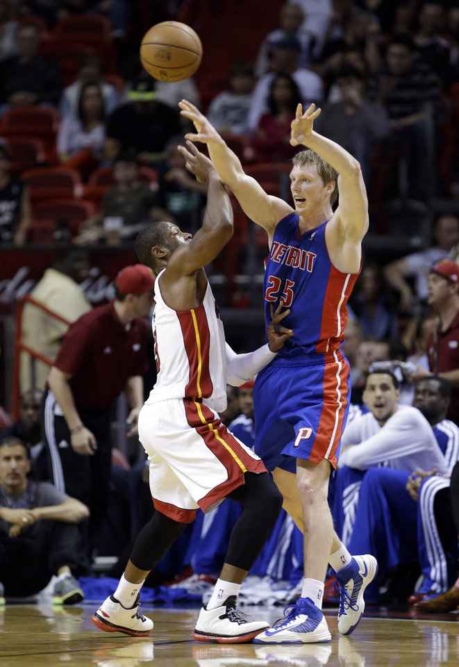 Photo - Detroit Pistons forward Kyle Singler (25) passes past Miami Heat guard Dwyane Wade during the first half of an NBA basketball game, Friday, Jan. 25, 2013, in Miami. (AP Photo/Wilfredo Lee)