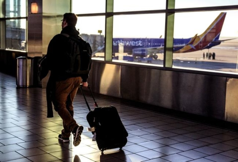 Photo -  A travelers makes his way through the Will Rogers World Airport terminal to catch a flight out of Oklahoma City. [Chris Landsberger/The Oklahoman]