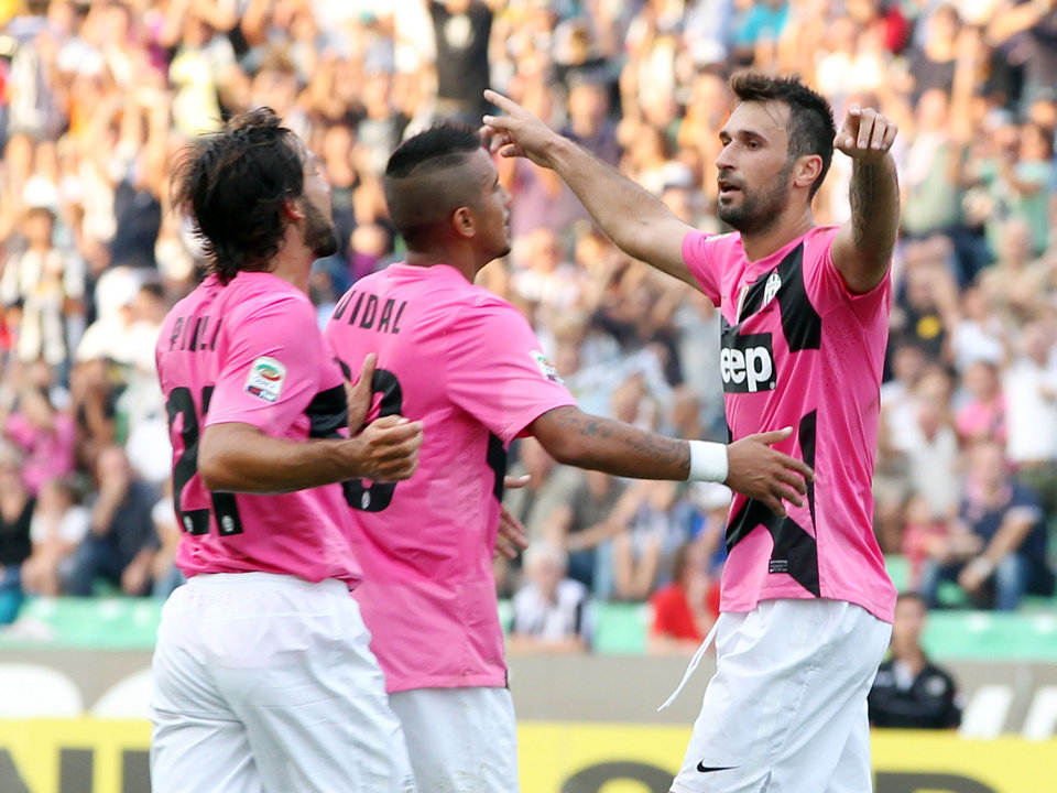 Photo -   Juventus Mirko Vucinic, of Montenegro, right, celebrates with teammates Arturo Vidal, center, and Andrea Pirlo after scoring during a Serie A soccer match between Udinese and Juventus at the Friuli Stadium in Udine, Italy, Sunday, Sept. 2, 2012. (AP Photo/Paolo Giovannini)