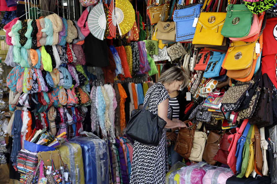 A woman looks through a display of purses on Canal Street in New York, Tuesday, June 4, 2013. Bargain hunters from around the world flock to Manhattan's Chinatown for legally sold bags, jewelry and other accessories bursting onto sidewalks from storefronts along Canal Street. (AP Photo/Seth Wenig)