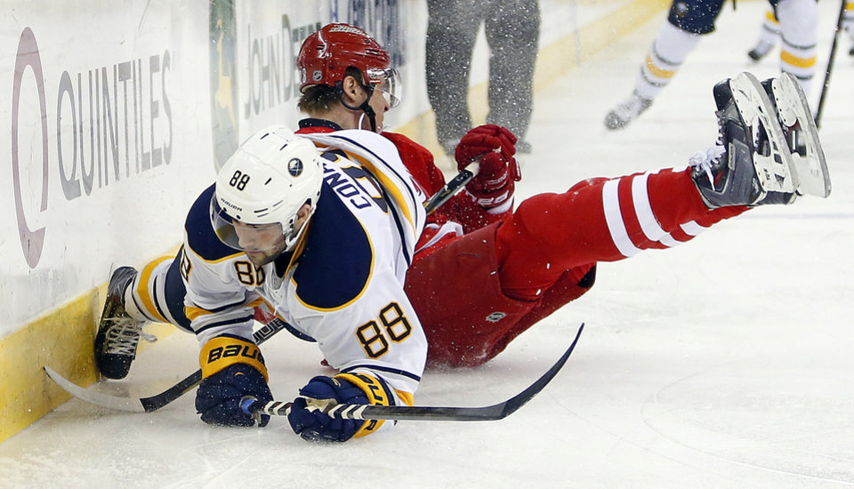 Photo - Buffalo Sabres' Cory Conacher (88) is taken down by Carolina Hurricanes' Alexander Semin, of Russia, during the first period of an NHL hockey game in Raleigh, N.C., Thursday, March 13, 2014. (AP Photo/Karl B DeBlaker)