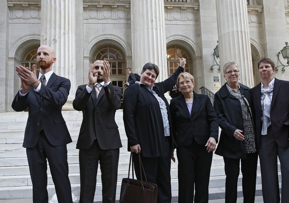 Photo - Plaintiffs challenging Utah's gay marriage ban, from left, Derek Kitchen, his partner Moudi Sbeity, Kate Call, her partner Karen Archer, Laurie Wood and her partner Kody Partridge stand together after leaving court following a hearing at the U.S. Circuit Court of Appeals in Denver, Thursday, April 10, 2014. The court is to decide if it agrees with a federal judge in Utah who in mid-December overturned a 2004 voter-passed gay marriage ban, saying it violates gay and lesbian couples' rights to due process and equal protection under the 14th Amendment. (AP Photo/Brennan Linsley)