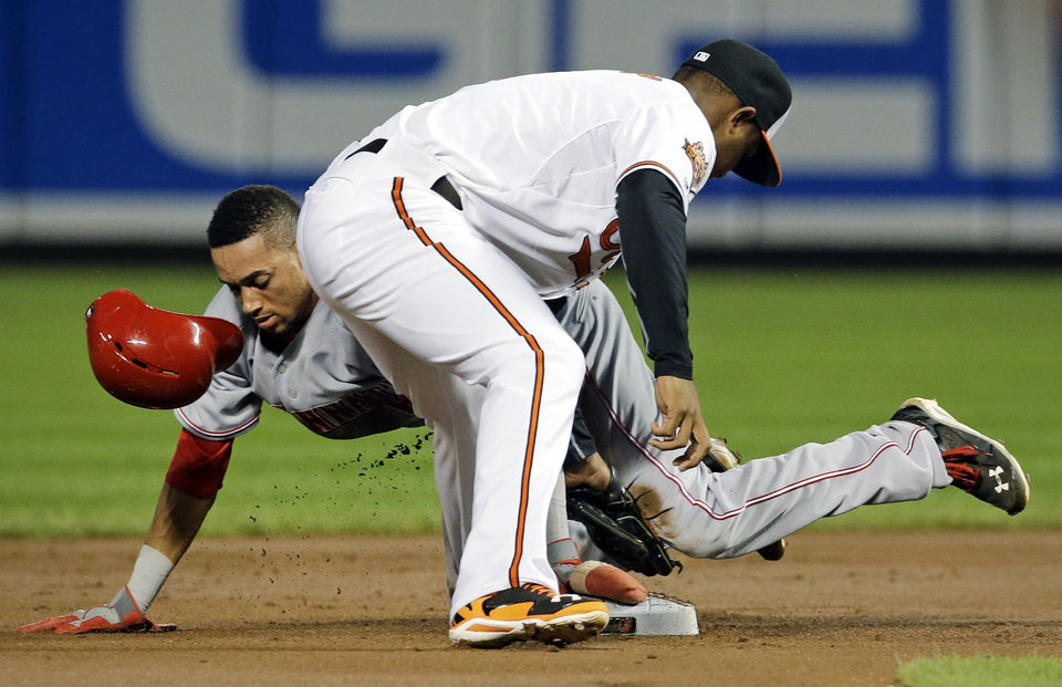Photo - Cincinnati Reds' Billy Hamilton, back, beats a tag by Baltimore Orioles second baseman Jonathan Schoop as he steals second in the first inning of an interleague baseball game, Tuesday, Sept. 2, 2014, in Baltimore. (AP Photo/Patrick Semansky)