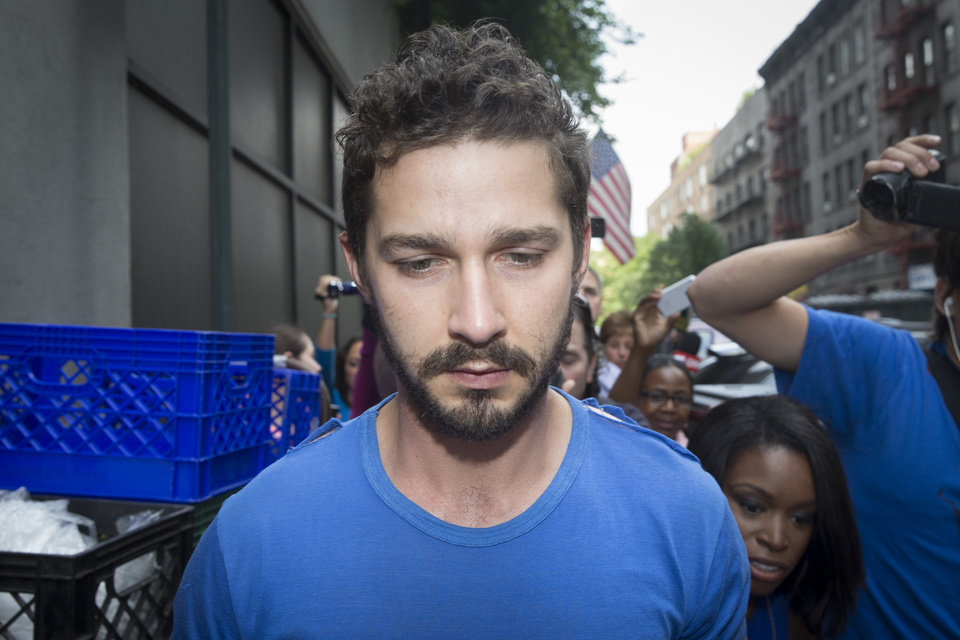 Photo - Actor Shia LaBeouf is followed by media after leaving Midtown Community Court following his arrest the previous day for yelling obscenities at the Broadway show