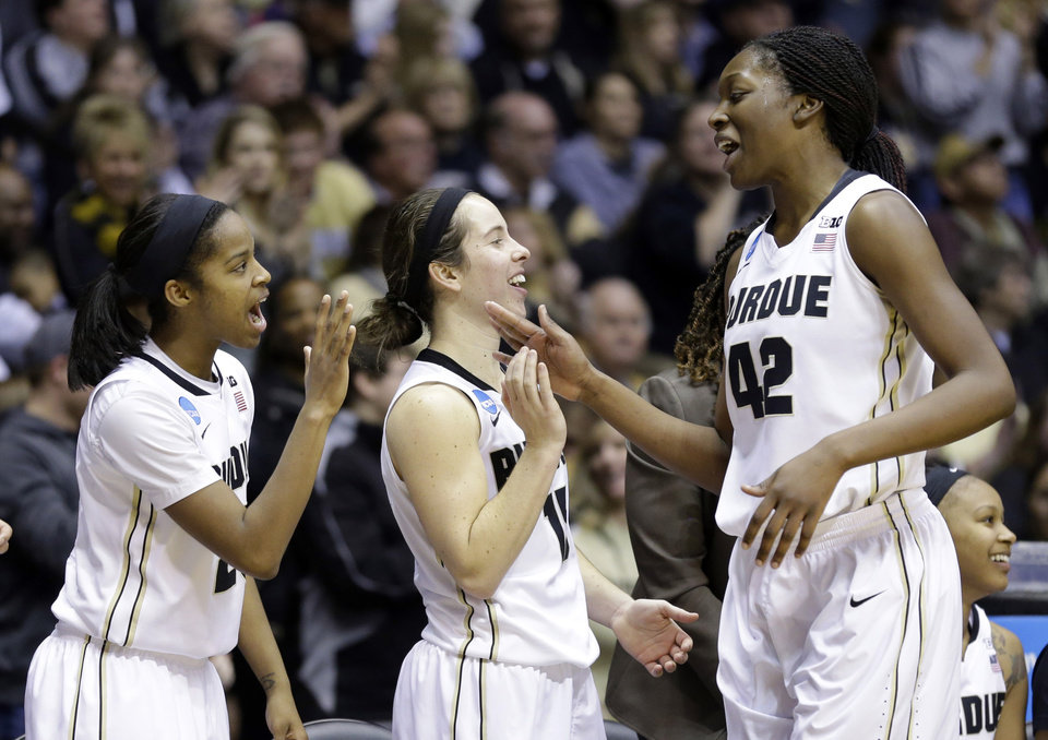 Photo - Purdue forward Camille Redmon, right, celebrates with teammates guard April Wilson. left, and guard Courtney Moses as she leaves the game during the second half of a first-round game against Akron in the NCAA women's college basketball tournament in West Lafayette, Ind., Saturday, March 22, 2014. Purdue defeated Akron 84-55. (AP Photo/Michael Conroy)