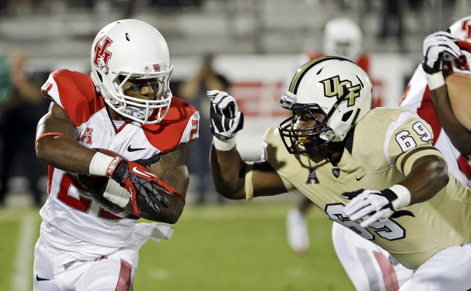 Photo - Houston running back Ryan Jackson, left, looks for a way around Central Florida's Thomas Niles (69) during the first half of an NCAA college football game in Orlando, Fla., Saturday, Nov. 9, 2013. (AP Photo/John Raoux)