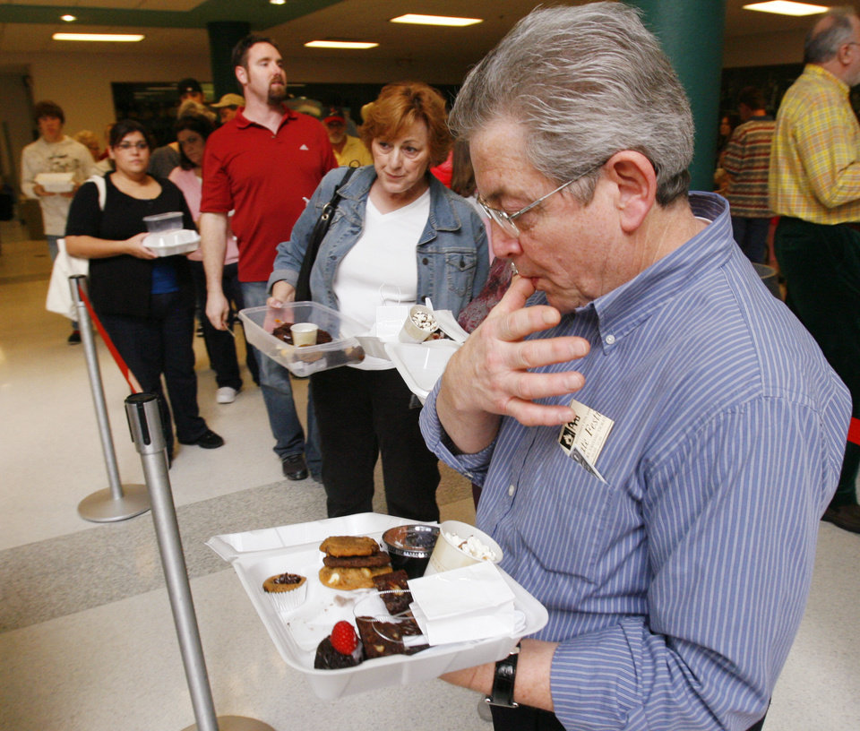 Photo - Rick Miller finds the treats at the 27th Annual Chocolate Festival benefiting the Firehouse Art Station finger-licking good in Norman, Okla. on Saturday, Feb. 7, 2009.   Photo by Steve Sisney, The Oklahoman