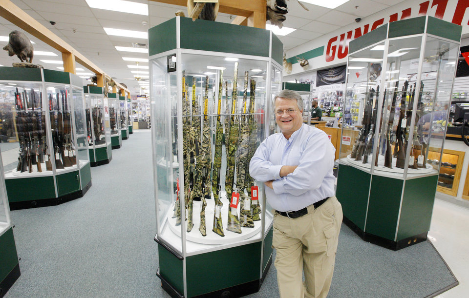Photo -  Miles Hall, founder and president of H & H Gun Range, leans against a display case in his store.   PAUL B. SOUTHERLAND -