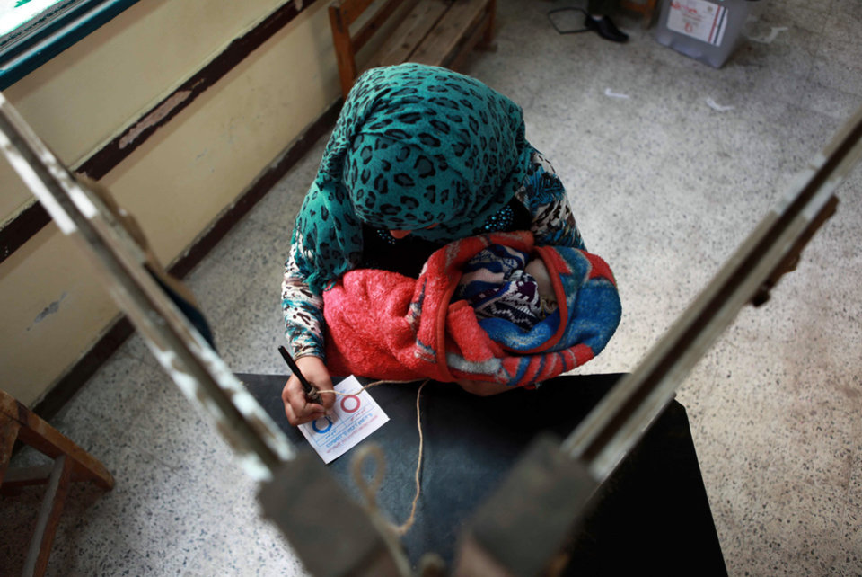 Photo - An Egyptian woman holds a child as she casts her vote in the country's constitutional referendum in Hawamdaya, 25 miles (40 kilometers) south of Cairo, Egypt, Tuesday, Jan. 14, 2014. Egyptians formed long lines Tuesday outside polling stations across much of the country to vote on a new constitution that represents a key milestone in a military-backed roadmap put in place after the ouster of Egypt's Islamist president in a coup last July. (AP Photo/El Shorouk Newspaper, Sabry Khaled)  EGYPT OUT