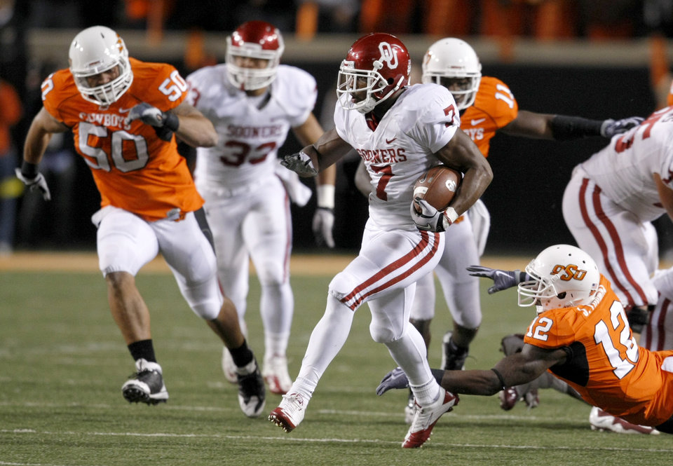 Oklahoma's Demarco Murray (7) runs past Oklahoma State's Johnny Thomas (12) and Oklahoma State's Jamie Blatnick (50) during the Bedlam college football game between the University of Oklahoma Sooners (OU) and the Oklahoma State University Cowboys (OSU) at Boone Pickens Stadium in Stillwater, Okla., Saturday, Nov. 27, 2010. Photo by Bryan Terry, The Oklahoman
