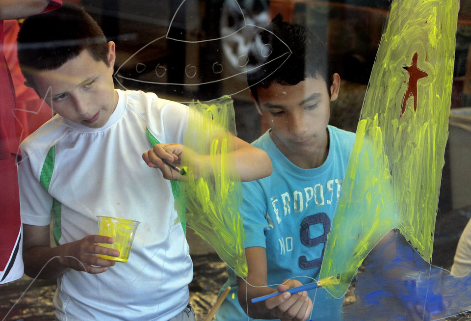 Above: Jesus De La Torre, 11, and Baltazar Nino, 14, paint a mural at Southern Oaks Library at a summer reading program kickoff event Wednesday.