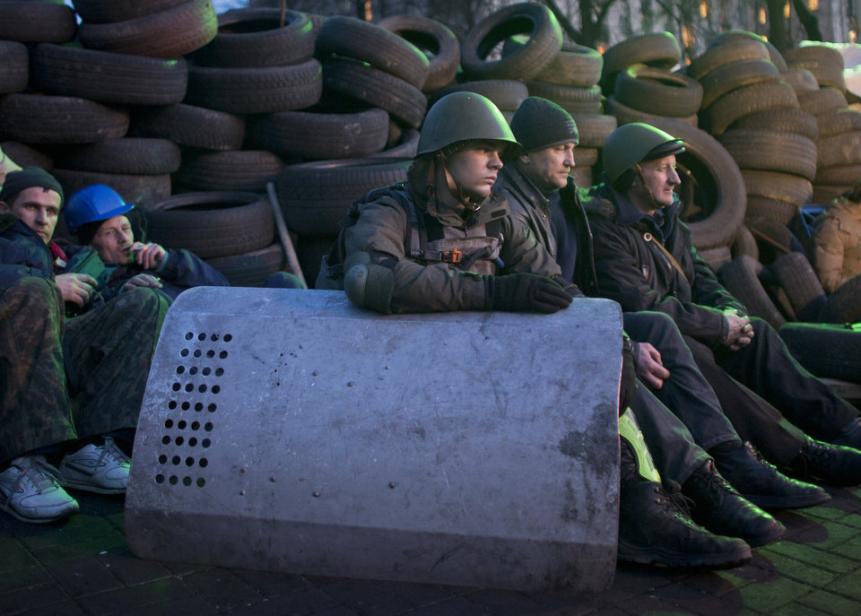 Photo - Anti-government protesters rest at a barricade in central Kiev, Ukraine, Friday, Feb. 21, 2014. Ukraine's bloody political crisis moved swiftly toward a possible solution Friday as the opposition signed a deal with the embattled president, and parliament changed the constitution and opened the way for the release of ex-Prime Minister Yulia Tymoshenko. (AP Photo/Darko Bandic)