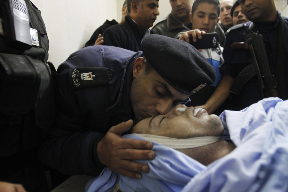 Photo -   Palestinian policeman kisses Rushdi Tamimi who died of his injuries sustained two days ago during clashes with Israeli security forces in Nabi Saleh. West Bank, in a Ramallah hospital, Monday, Nov. 19, 2012. (AP Photo/Nasser Shiyoukhi)
