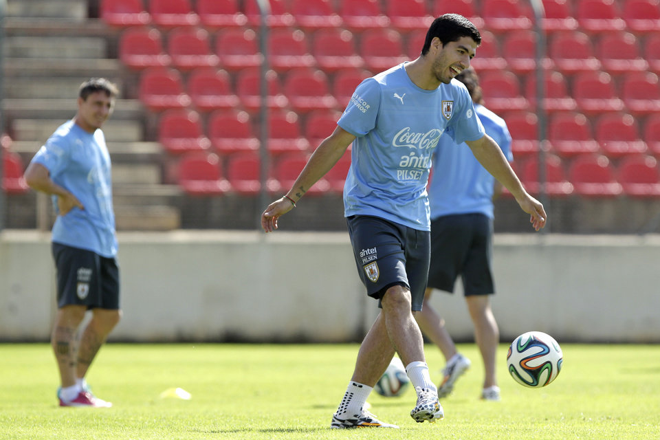 Photo - Luis Suarez, front, and Cristian Rodriguez, behind left, of a Uruguay's national team, train at Arena do Jacare Stadium, for the Brazil 2014 World Cup in Sete Lagoas, Brazil, Saturday, June 21, 2014. Uruguay plays in group D at the 2014 soccer World Cup. (AP Photo/Bruno Magalhaes)