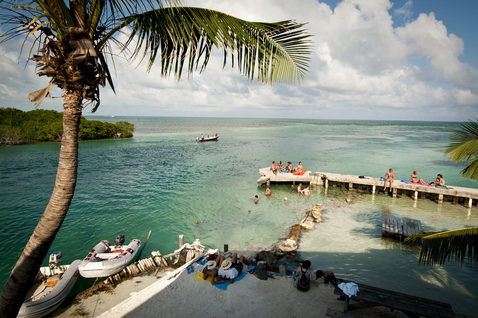 Photo - This undated photo provided by The Belize Tourism Board shows vacationers relaxing at Caye Caulker, Belize. The beach town is a laid-back, low-cost base for tourists looking to explore a nearby barrier reef. (AP Photo/The Belize Tourist Board)