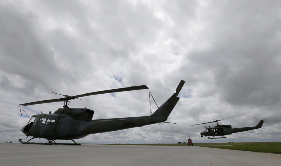 Photo - This photo taken June 25, 2014 shows a Vietnam-era Huey helicopter taking off at Minot Air Force Base, N.D. A fleet of seven of the aging helicopters are used to support the 150 Minuteman missiles carrying nuclear warheads which are deployed in the countryside surrounding Minot Air Force Base. (AP Photo/Charlie Riedel)